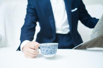 コーヒーカップを持ちながら新聞を見る男性