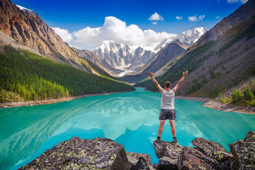 Hiker standing with raised hands near beautiful mountain lake