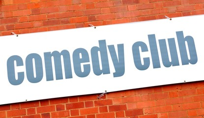 Comedy club sign against red brick wall