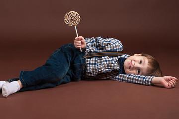 fashion boy lying on the floor with a lollipop