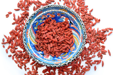 Dried Tibetan goji berries in ceramic bowl on white background