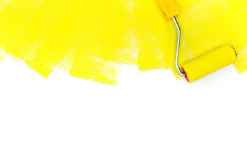 painting a wall with roller and yellow paint