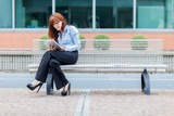 Businesswoman with tablet pc is sitting outside on a metal bank