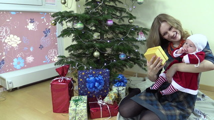 Smiling woman show her lovely baby gift box near Christmas tree