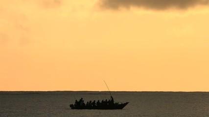 Silhouette of a small fishing boat at sunrise, Zanzibar island