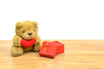 Red gift box and teddy bear on wooden table