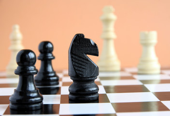 Chess pieces on a chessboard on a light background.