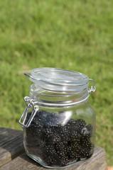 blackberries in glass pot on garden table