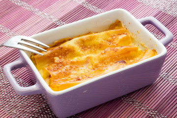Cannelloni baked with ham and cheese