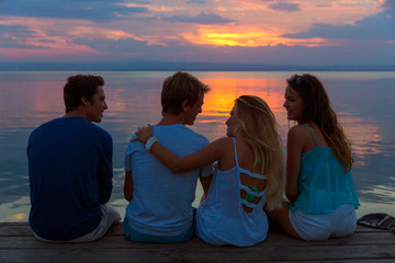 Friends group rear view at sunset fun together