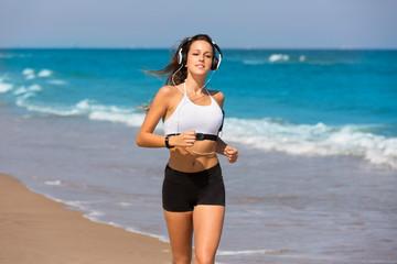 Brunette girl running on the beach headphones
