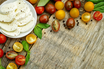 wood background with tomatoes, Basil, mozzarella.