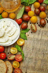 wood background with tomatoes, Basil, mozzarella, bread