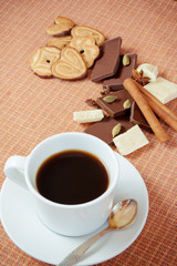 Cup of coffee with cookies, chocolate and spices on a table. Sel