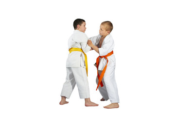 Boys are training Judo techniques against a white background