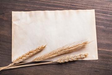 blank sheet of paper with ears wheat rye on vintage wooden board
