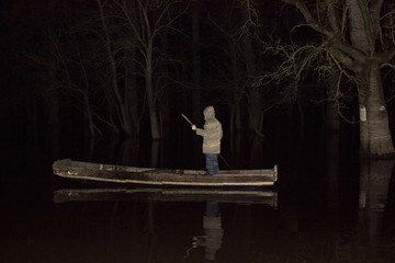 Man standing in the boat on lake in night