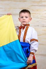 Cute child holding the national flag of Ukraine
