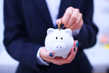 Businesswoman putting  money into a piggy bank isolated on white