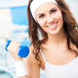 Young happy woman in fitness wear exercising