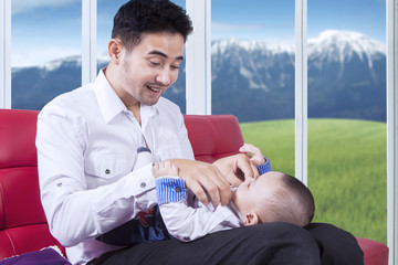 Attractive father replace his baby wear