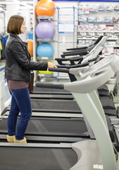 woman buys a treadmill in a sports shop