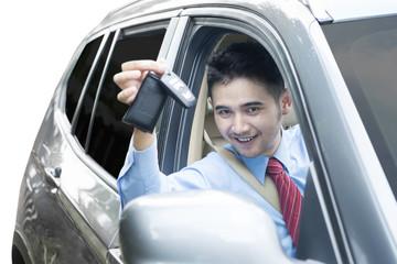 Businessman showing a car key inside car