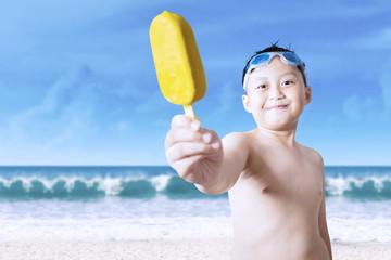 Cheerful little boy showing ice cream