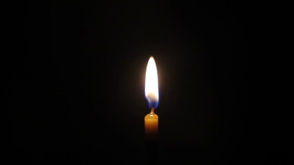 Wax candles burning on a black background, slow motion