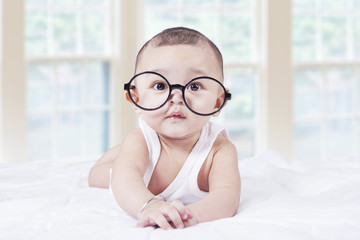 Little baby with glasses lying on bed