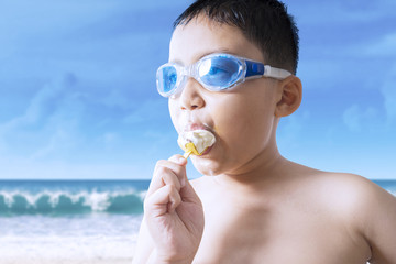 Male kid bites ice cream at seaside