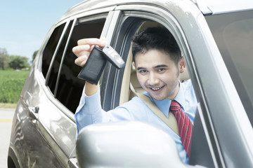Man inside a car and showing a car key