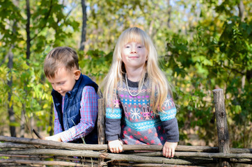 Kids in Autumn Outfit Playing at the Wooden Fence