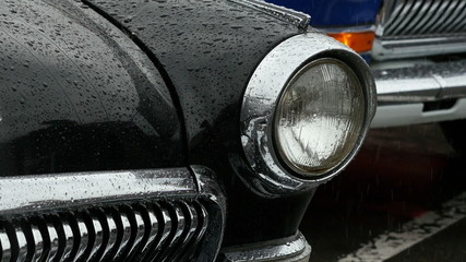 Close-up of headlight and front side of old car in the rain.