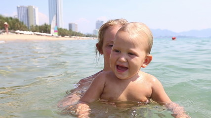 young blonde mother bathes little daughter in sea