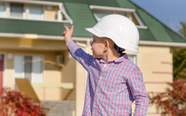 Boy Wearing Hard Hat Presenting Finished House