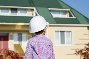 Boy Wearing Hard Hat Standing in front of House