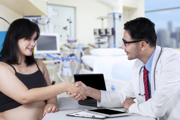 Pregnant woman handshaking with doctor