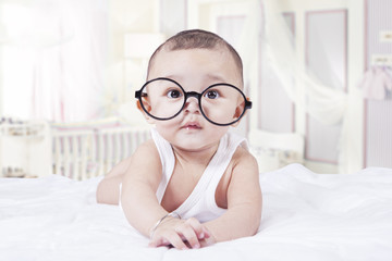 Sweet baby with glasses in bedroom