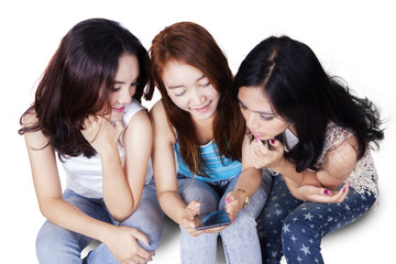 Teens reading message together on cellphone