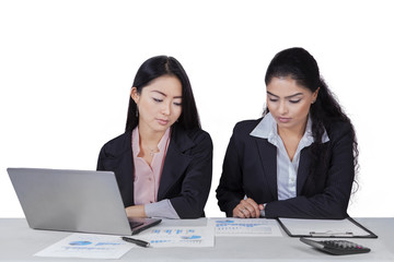 Two women working with documents on desk