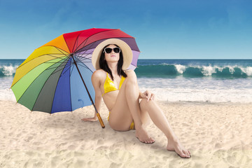 Woman sitting under umbrella at coast