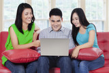 Young people with laptop sitting on sofa