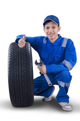 Young mechanic with tire showing thumb up