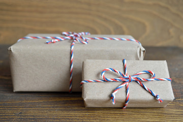 Brown paper parcel tied with string on wooden background