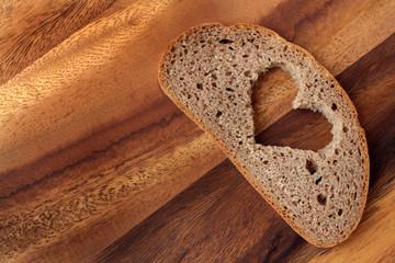 Brotscheibe mit Herz auf Holzbrett