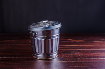 Trash can on wooden table background