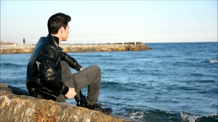 Young man at the seaside overlooking the ocean or sea