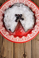 Chocolate pie with blueberry and icing sugar cut in red plate