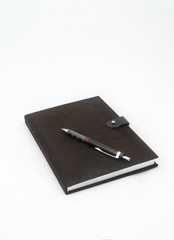 Brown notebook and pencil on white background